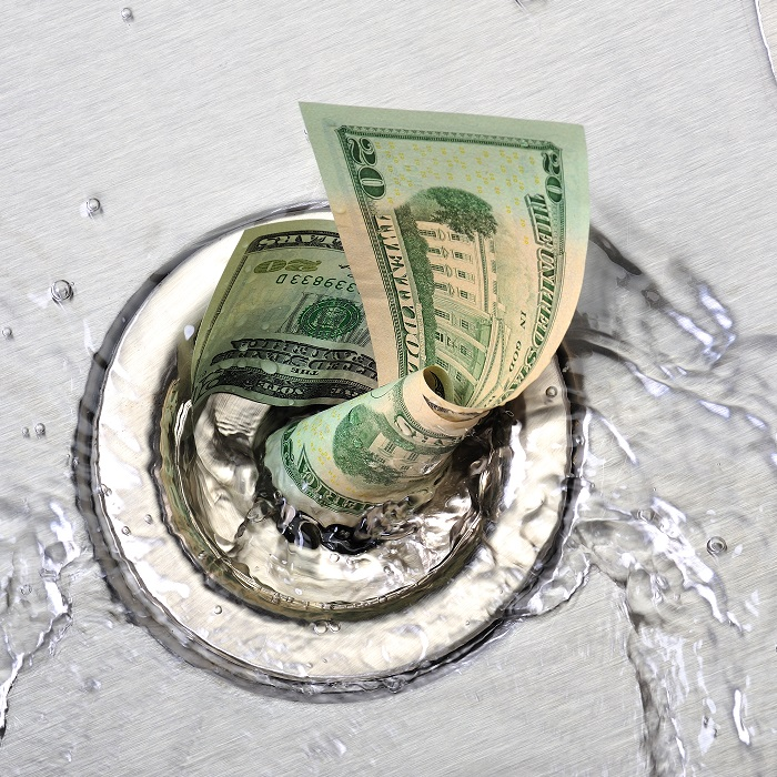 Wasted money going down the sink drain showing sales leakage