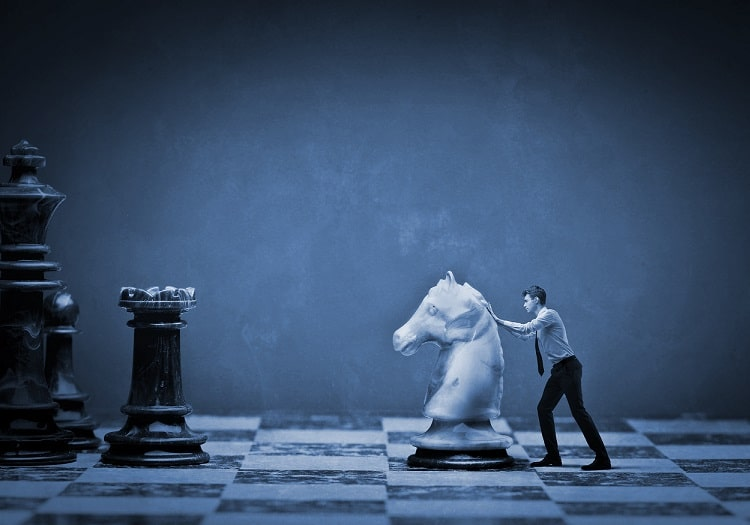 man moving a giant chess piece on chess board showing corporate strategy