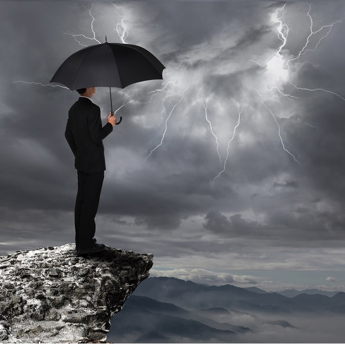Man standing under umbrella thinking of accurate sales forecasts