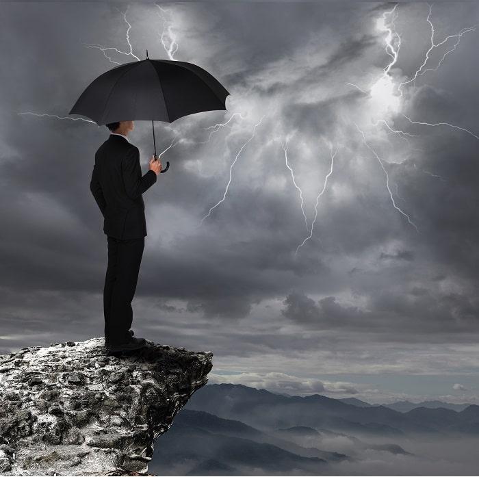 man standing under umbrella looking at a storm