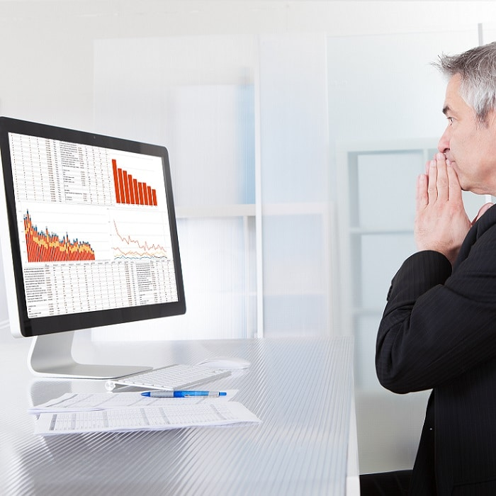 Businessman looking at screen with sales revenue falling