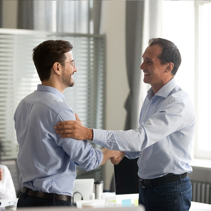 CEO Congratulating a young man on his promotion
