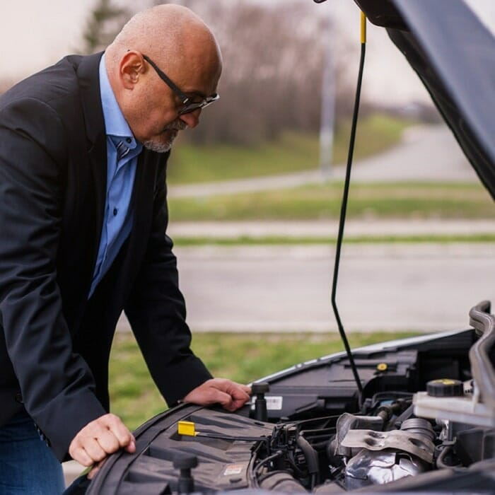 Businessman looking under bonnet of car to see why it stalled
