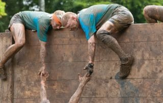 people climbing over wall in a survival race