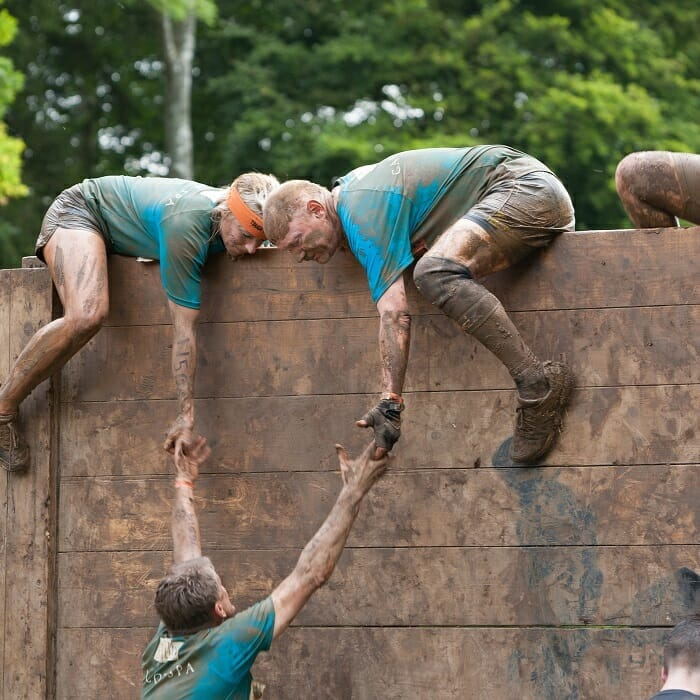 people climbing over wall as a metaphor to business survival or business growth in a survival race