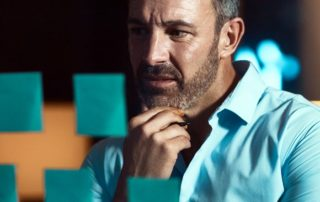 man using sticky notes to work on sales quota setting for team members